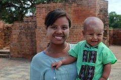 Niet geïdentificeerde smilling moeder en zoon met thanakha op hun gezichten in Myanmar Stock Afbeeldingen