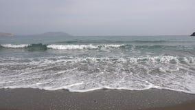Niet gehaaste golven van de Zwarte Zee die op de zandige kust in werking wordt gesteld Kalme bewolkte dag mist stock video