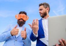 Niet professioneel gedrag Zakenman met ernstig laptop terwijl de partner belachelijke glazen grappig kijkt hoe royalty-vrije stock foto