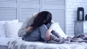 Niet succesvolle droevige vrouwenzitting bij grijze slaapkamer op bed stock videobeelden