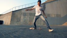 Niet succesvolle poging van een mannelijke tiener om een stunt op een skateboard uit te voeren stock footage