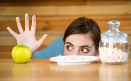 Niet zeker in haar keus Vitamine of suiker De vrouw kiest welk te eten voedsel De mooie vrouw verkiest appel boven heemst stock afbeelding