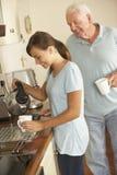 Nieta adolescente que comparte la taza de té con el abuelo en cocina Imagen de archivo