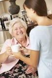 Nieta adolescente que hace abuela la bebida caliente en casa Imagen de archivo