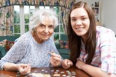 Nieta adolescente que hace el rompecabezas con la abuela Imagen de archivo