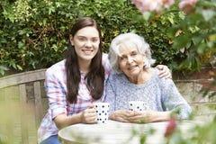 Nieta adolescente que se relaja con la abuela en jardín Imagen de archivo libre de regalías