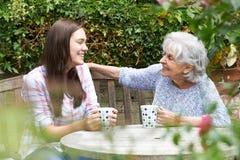Nieta adolescente que se relaja con la abuela en jardín Imágenes de archivo libres de regalías