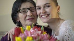 Nieta con la abuela que sostiene las flores y que sonríe en cámara lentamente