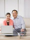 Nieta con la abuela y la computadora portátil Imágenes de archivo libres de regalías