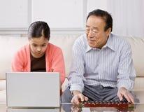 Nieta con la computadora portátil y el abuelo Imagen de archivo libre de regalías