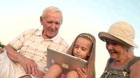 Nieta con la tableta de la PC y la abuela sorprendida almacen de video