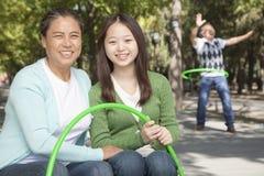 Nieta con los abuelos que juegan con el aro plástico en el parque Imágenes de archivo libres de regalías