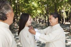 Nieta con los abuelos que practican a Tai Chi Imagen de archivo