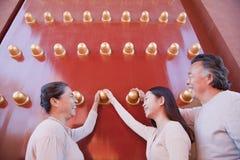 Nieta con los abuelos que se colocan al lado de las puertas rojas tradicionales y que llevan a cabo las manos Foto de archivo libre de regalías