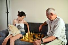 Nieta con un perro y un abuelo que juegan a ajedrez Fotos de archivo