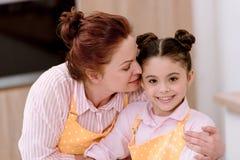 nieta de abarcamiento de la abuela pequeña mientras que cocina Imagen de archivo