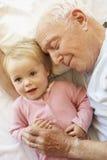 Nieta de abrazo de abuelo en cama fotografía de archivo