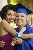 Nieta de abrazo graduada del mayor Fotografía de archivo libre de regalías