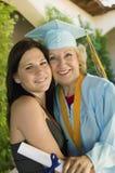 Nieta de abrazo graduada del mayor afuera Imagenes de archivo