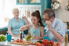 Nieta de enseñanza del abuelo a cocinar imagen de archivo