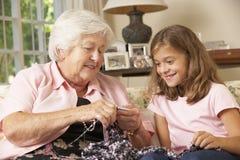A nieta de la abuela mostrando cómo hacer punto en casa Fotografía de archivo libre de regalías