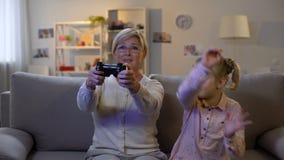 Nieta del trastorno que toma la palanca de mando de las manos de la abuelita, malentendido del juego almacen de video