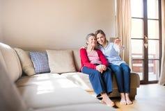 Nieta mayor de la abuela y del adulto con smartphone en casa Foto de archivo libre de regalías