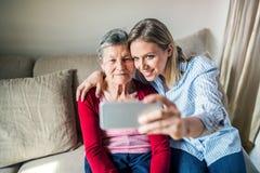 Nieta mayor de la abuela y del adulto con smartphone en casa Imagen de archivo