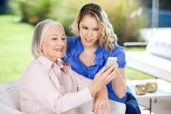 Nieta que ayuda a la nieta al usar Imagenes de archivo