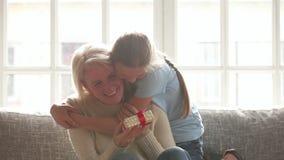 Nieta que hace la sorpresa que abraza a la vieja abuela feliz que presenta el regalo de cumpleaños almacen de video