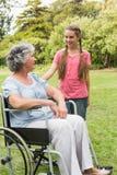 Nieta sonriente con la abuela en su silla de ruedas Imagen de archivo libre de regalías