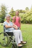 Nieta sonriente con la abuela en su silla de ruedas Fotos de archivo libres de regalías
