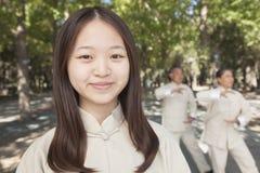 Nieta sonriente con los abuelos que practican a Tai Chi en el parque Imagen de archivo libre de regalías