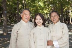 Nieta sonriente con los abuelos que practican a Tai Chi, mirando la cámara Imagenes de archivo