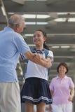 Nieta sonriente que abraza a su abuelo con la abuela en fondo Foto de archivo