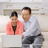 Nieta y abuelo en la computadora portátil Fotos de archivo libres de regalías