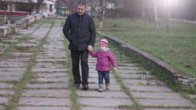 Nieta y abuelo que caminan en el parque de la ciudad que lleva a cabo las manos Cámara lenta metrajes