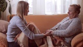 Nieta y su sentarse que habla de la abuela en el sofá metrajes
