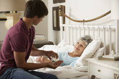 Nieto adolescente que da la medicación de la abuela en cama en casa Imagen de archivo libre de regalías
