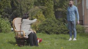 Nieto adulto que visita a su abuela, trayendo su ramo de tulipanes El hombre barbudo que incorpora la casa y el abrazo almacen de metraje de vídeo