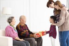 Nieto con los padres que dan un regalo a los abuelos fotografía de archivo libre de regalías