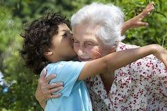 Nieto que abraza a su abuela en el parque Imagen de archivo