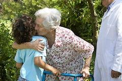 Nieto que abraza a su abuela en el parque del hospital Foto de archivo libre de regalías