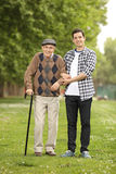Nieto que ayuda a su abuelo en el parque Foto de archivo libre de regalías