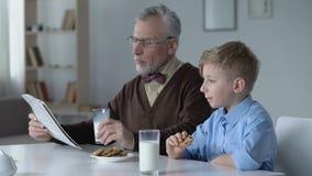 Nieto que come las galletas, para abuelo que espera para acabar de leer el periódico, familia almacen de video