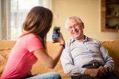 Nieto que fotografía al abuelo en su teléfono Imagen de archivo libre de regalías