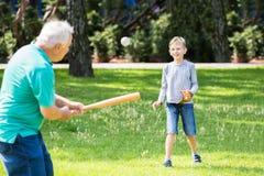 Nieto y abuelo que juegan a béisbol imagenes de archivo