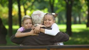 Nietos alegres que corren a su abuelo querido, abrazando detrás la visión metrajes