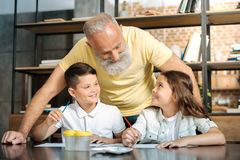 Nietos alegres que hablan con su abuelo mientras que pinta Imagenes de archivo