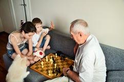 Nietos con el abuelo que juega a ajedrez Foto de archivo libre de regalías